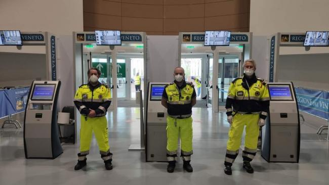 Tre volontari controllano l'ingresso del Pala acque per misurazione temperatura, disinfezione mani e indicazioni